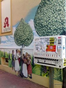 Pared de una farmacia con mural ñoño y... máquina de tabaco!